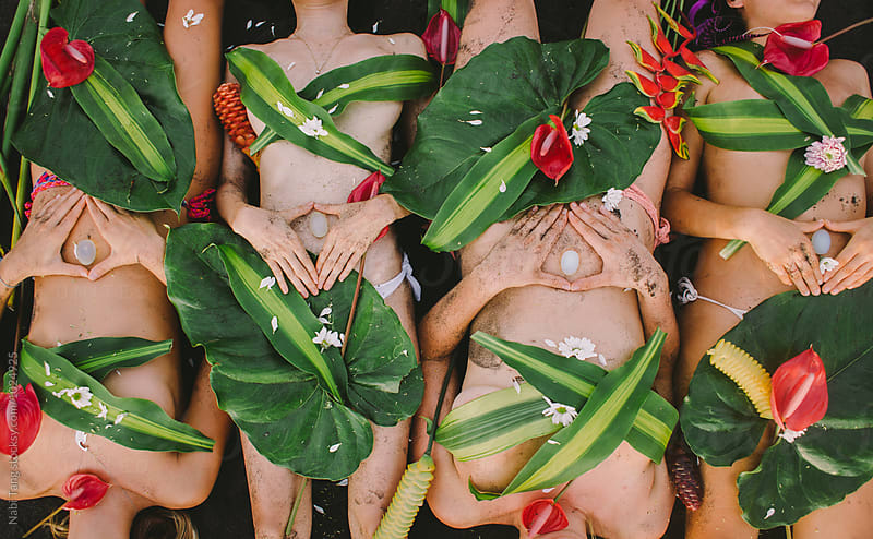 Beautiful hippie women group laying on the beach covered by plant and flowers holding healing crystal by Nabi Tang for Stocksy United