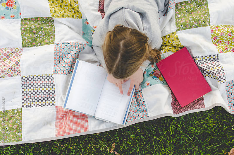 Girl reading on a picnic blanket by Lindsay Crandall for Stocksy United