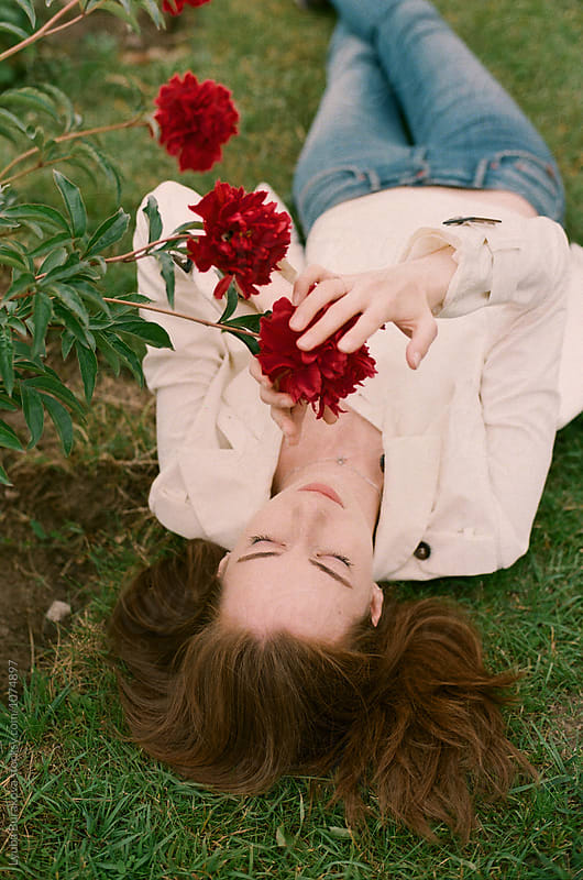 Young woman lying at the peony garden by Lyuba Burakova for Stocksy United