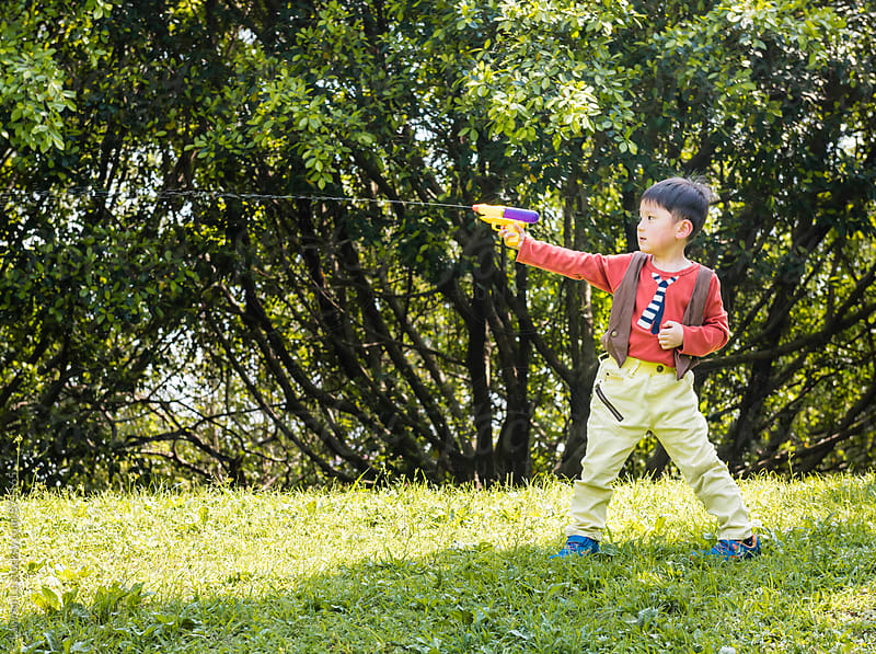 Kid spouting water gun on green grass at park by Lawren Lu for Stocksy United