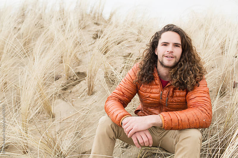Young curly man in dunes by Ivar Teunissen for Stocksy United