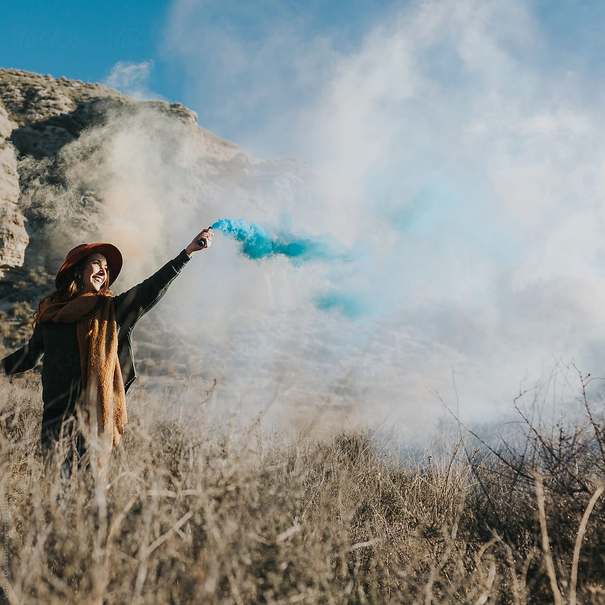 Cheerful teenager playing with color smoke bombs in the countryside