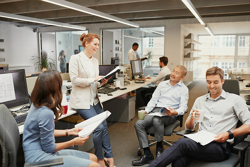 Casual team meeting in open office discussing business by Aila Images for Stocksy United