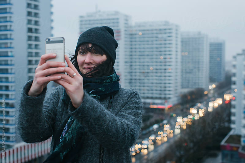 Cute Woman Taking Selfie on Berlin Rooftop on Rainy Winter Day by VISUALSPECTRUM for Stocksy United
