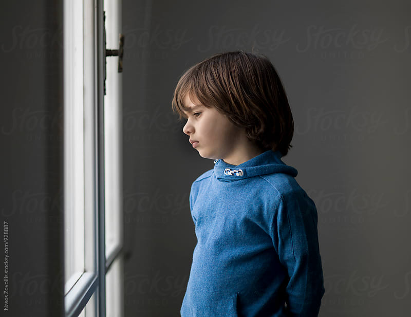 Portrait of a boy looking outside of the window by Nasos Zovoilis for Stocksy United