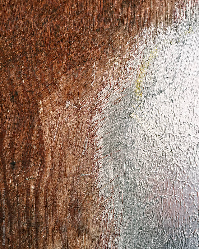 Metallic paint covering graffiti tags on plywood wall, close up by Paul Edmondson for Stocksy United