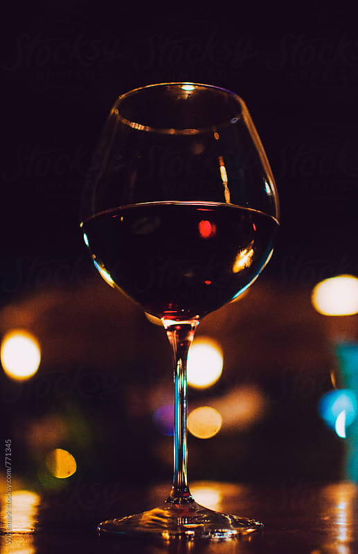 Glass of red wine on the table at night by Wizemark for Stocksy United