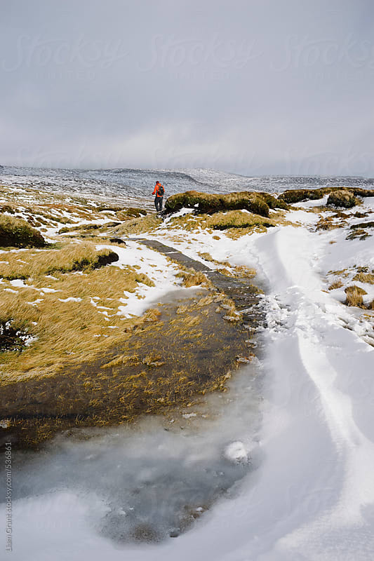 Male standing on the snow covered moorland of Bleaklow. by Liam Grant for Stocksy United