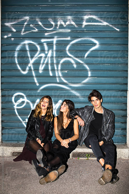Group of friends sitting together in the street at night by michela ravasio for Stocksy United