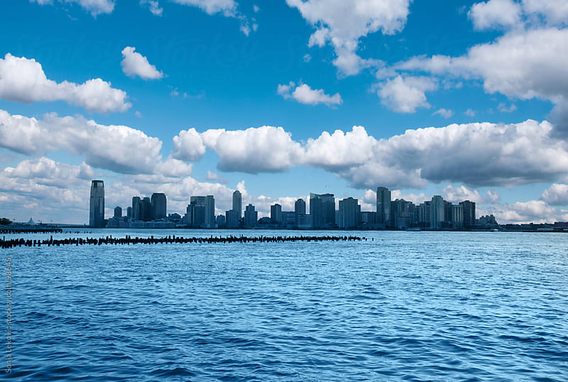 manhattan cityscape between the ocean and the blue sky by Sonja Lekovic for Stocksy United