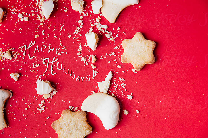 Holiday wishes written with whipped cream and sweet cookies on red by Beatrix Boros for Stocksy United