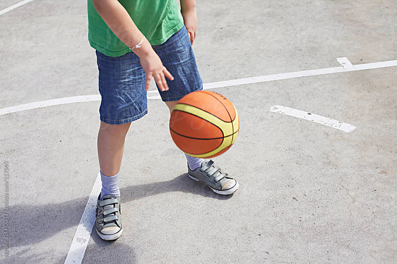 close up of young boy bouncing a basketball by Natalie JEFFCOTT for Stocksy United