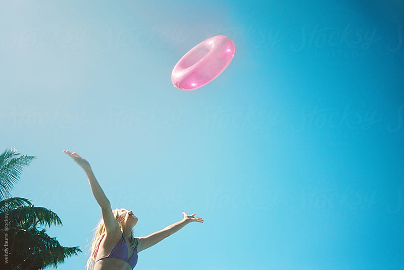 blonde girl in bikini throwing pink floatie in air against blue sky by wendy laurel for Stocksy United