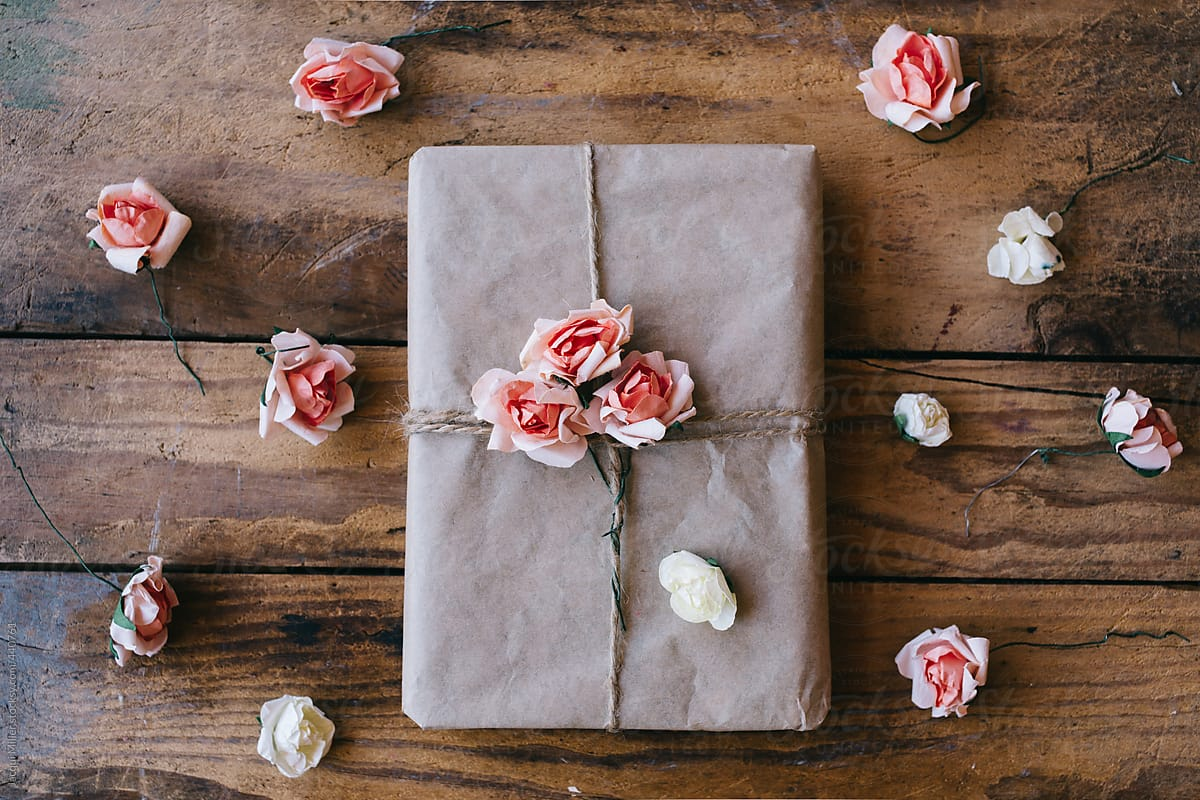 Gift Wrapped In Brown Paper And Decorated With Flowers Made From