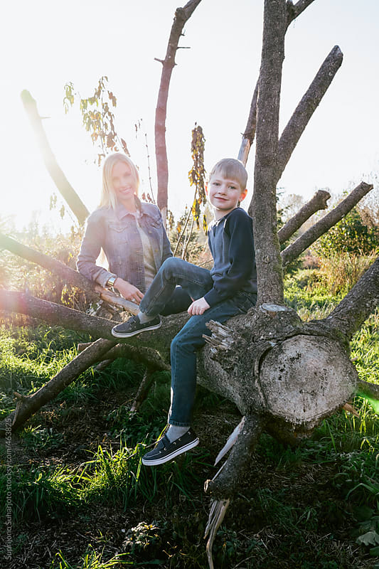 Portrait of a happy mother and her son sitting on a tree by Suprijono Suharjoto for Stocksy United