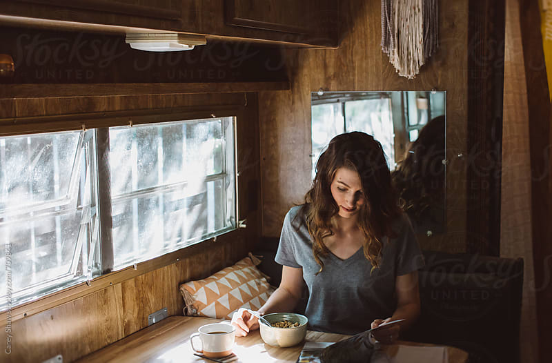 Woman reading and eating breakfast by Carey Shaw for Stocksy United