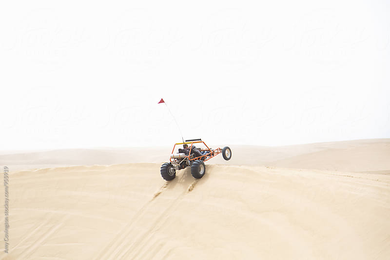 A sand rail catching air as it jumps a sand dune by Amy Covington for Stocksy United