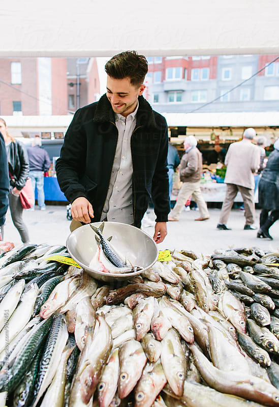 Young man beying fish on the fish market by Denni Van Huis for Stocksy United