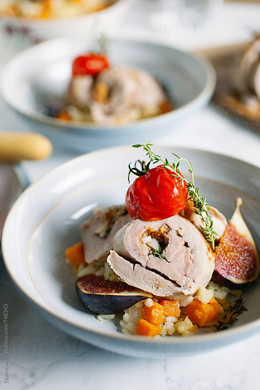 Roast pork tenderloin stuffed with figs and shallots served with sweet potato risotto. by Darren Muir for Stocksy United