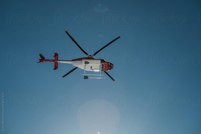 Looking up at a helicopter flying overhead by Riley J.B. for Stocksy United