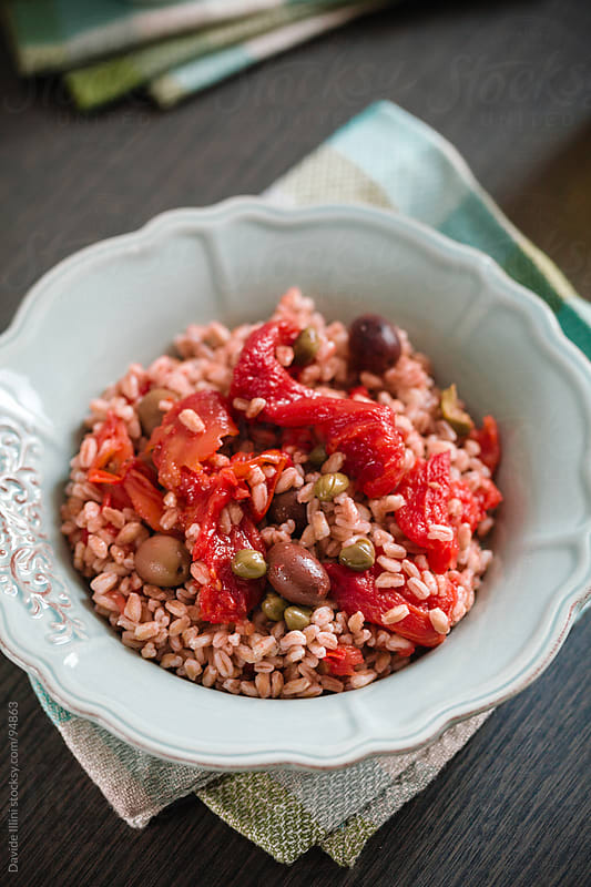 Spelt salad with tomatoes, olives and capers by Davide Illini for Stocksy United