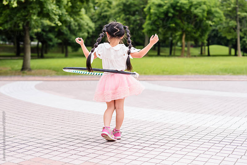 Portrait of little girl in pink precticing with hulahoop on park by Lawren Lu for Stocksy United