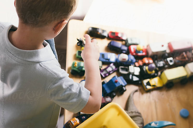 Little boy playing with toy cars by Gary Radler Photography for Stocksy United