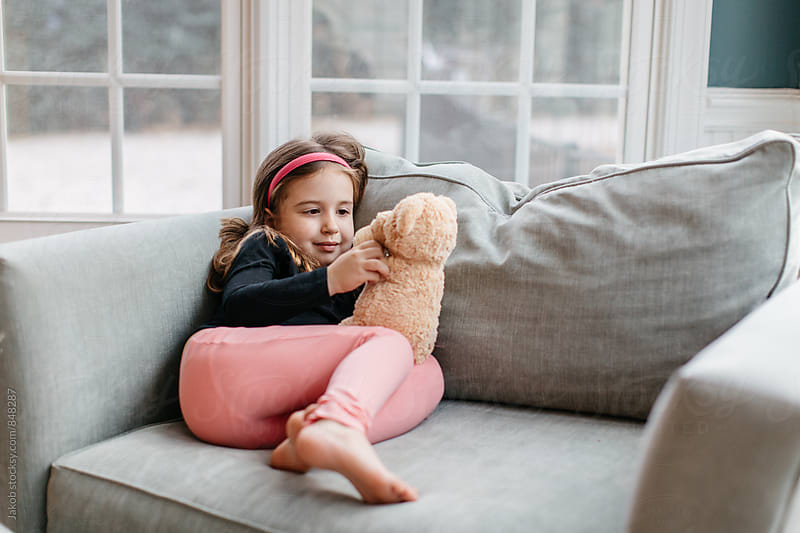 Cute young girl laying on a big chair playing with her teddy bear by Jakob for Stocksy United