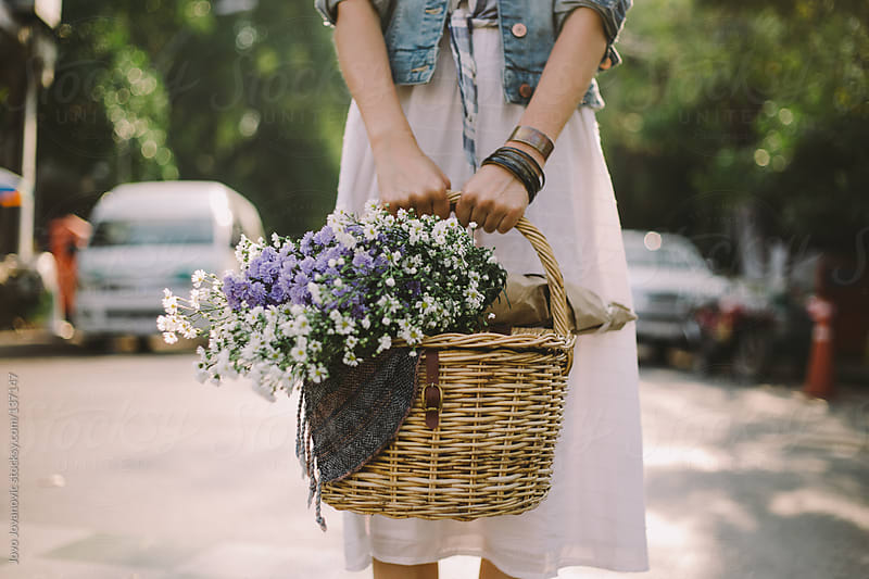 Girl holding a basket full of wildflowers by Jovo Jovanovic for Stocksy United