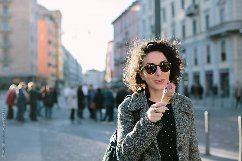 Woman eating ice cream on the street by Davide Illini for Stocksy United