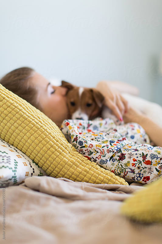 Woman playing with dog on the bed by Javier Pardina for Stocksy United