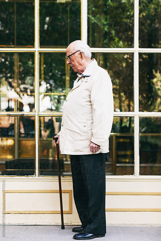 Side view of an elderly man standing with a stick in front of a door. by BONNINSTUDIO for Stocksy United
