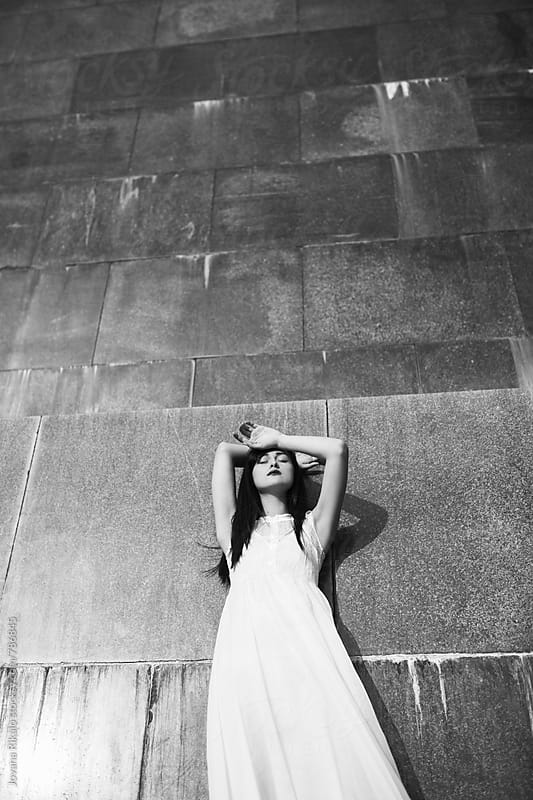 Black and white portrait of a young woman in a white dress by Jovana Rikalo for Stocksy United