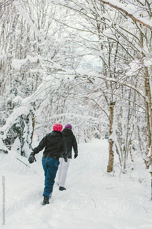 Two Women  on Snowy Path in Forest by Stephen Morris for Stocksy United