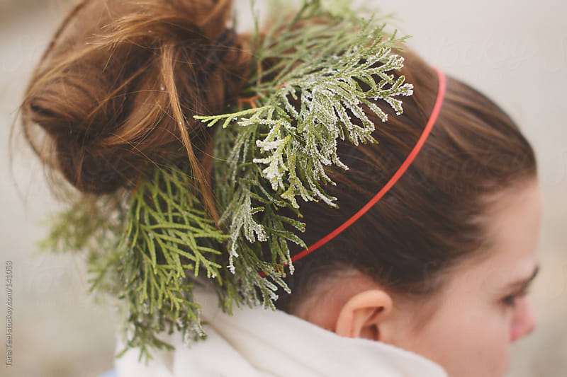 A wreath of frosty evergreen sprigs decorate a girl's hair by Tana Teel for Stocksy United
