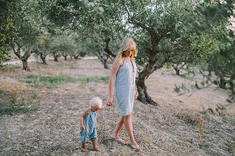 Woman and her little daughter walking through the olive grove  by Evgenij Yulkin for Stocksy United