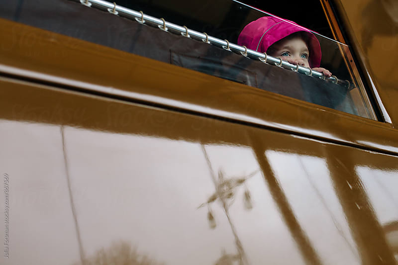 Little girl peeks from a train window. by Julia Forsman for Stocksy United