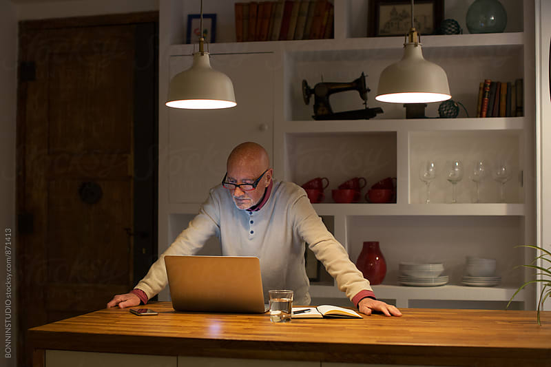 Elderly man working at home office in the late afternoon. by BONNINSTUDIO for Stocksy United