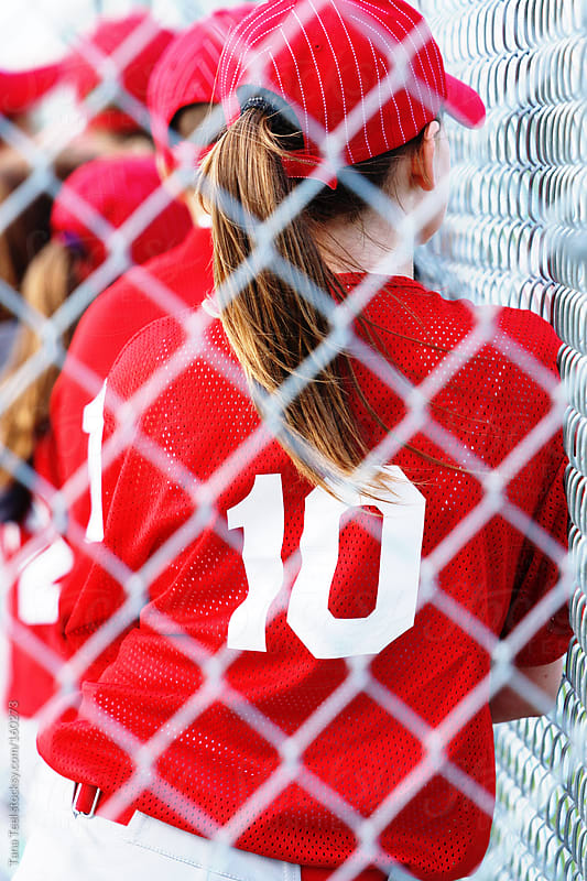 A teenage girl playing baseball leans against the fence by Tana Teel for Stocksy United
