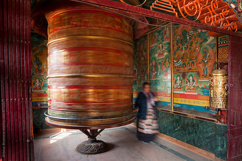 Woman rotates the large Praying wheel inside a stupa. by Shikhar Bhattarai for Stocksy United