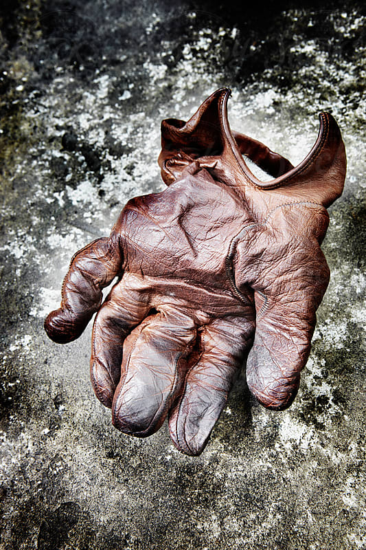 A leather glove on stone by James Ross for Stocksy United