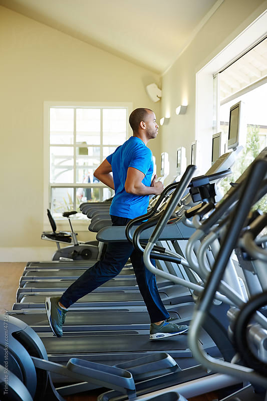 Man working out at gym at luxury resort  by Trinette Reed for Stocksy United