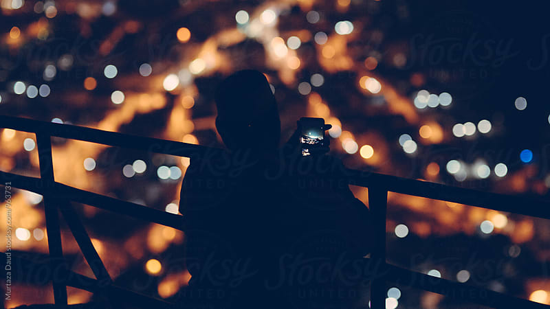 A silhouette of a man taking a photo with his mobile phone at night by Murtaza Daud for Stocksy United