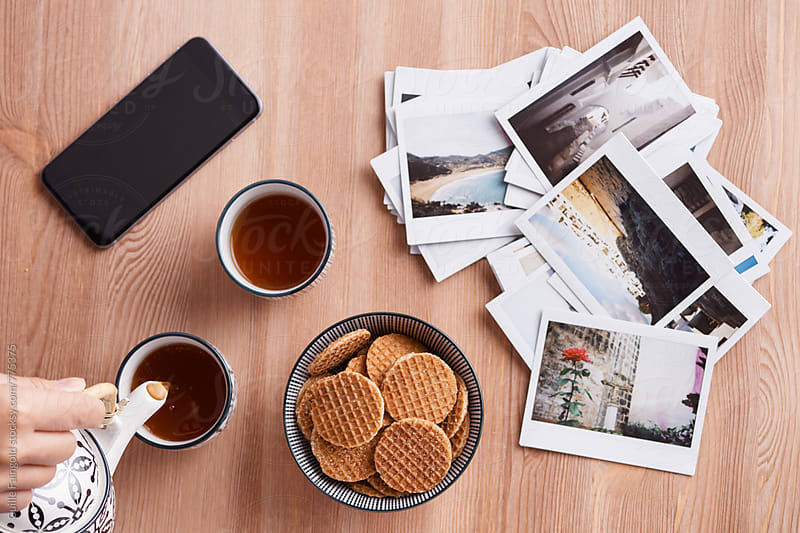 tea time: tea, cookies, mobile phone and some polaroids by Guille Faingold for Stocksy United