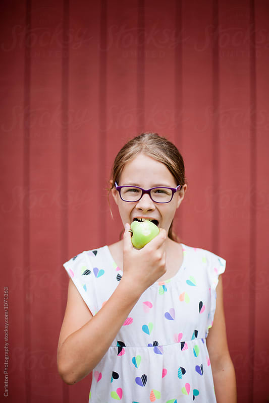 Eleven  year old girl bites into freshly picked green apple by Carleton Photography for Stocksy United