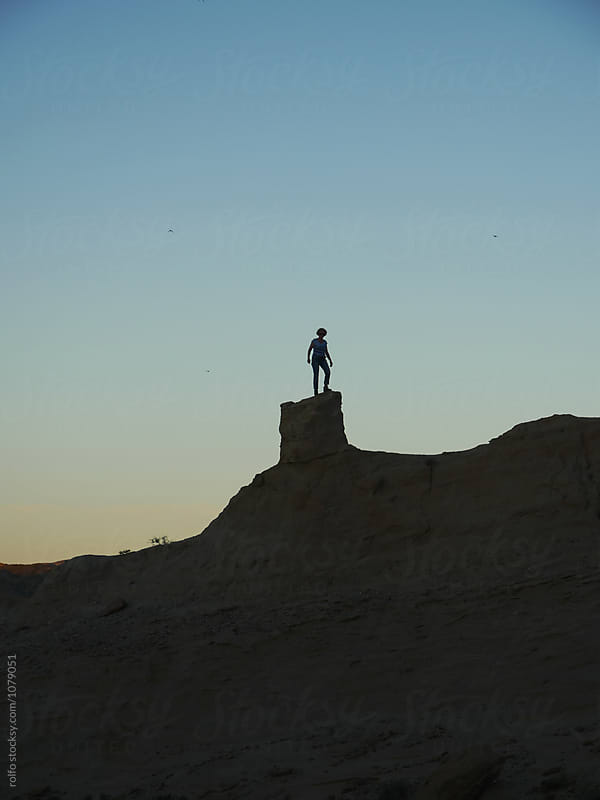Woman standing on sandy peak by rolfo for Stocksy United
