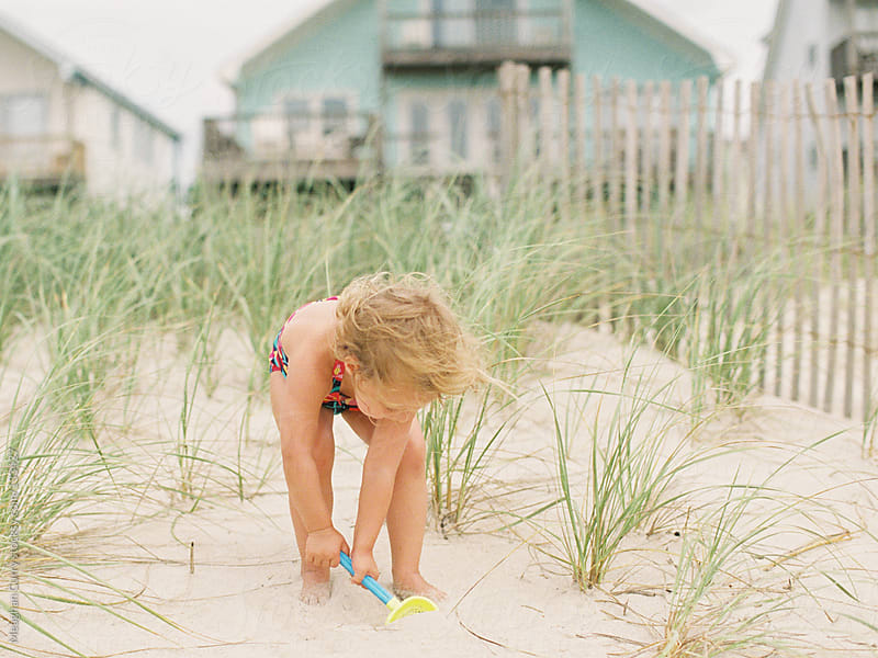 little girl playing at the beach in the sand by Meaghan Curry for Stocksy United