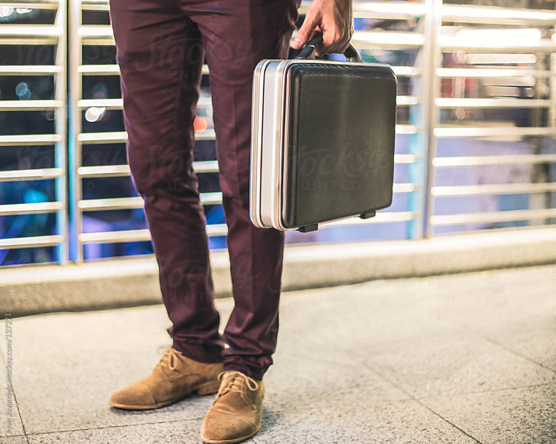Young man standing and holding his suitcase. by Jovo Jovanovic for Stocksy United