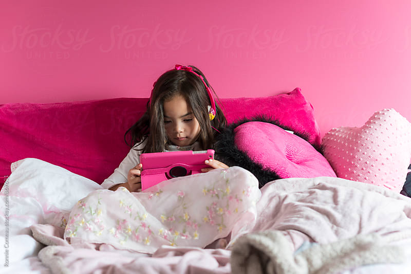 Girl In Pink Room On Electronics by Ronnie Comeau for Stocksy United