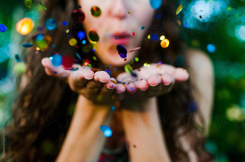 A young woman blowing glitter confetti by Chelsea Victoria for Stocksy United